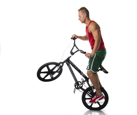wheelie: Handsome Athletic Young Man Doing Tricks and Popping a Wheelie on Bicycle in Studio with White Background