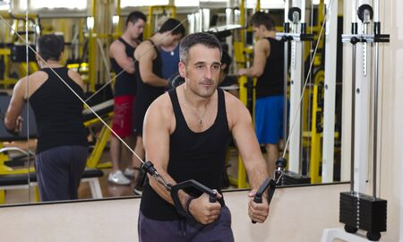 pecs: Middle aged man working out with gym equipment, exercising pecs muscles with cables