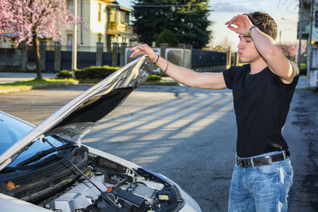 engine bonnet: Handsome young man trying to repair a car engine, looking inside open bonnet