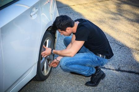 en cuclillas: Hombre joven en ropa ocasional Eyacular Además de la rueda de un Cambio de su coche blanco Neumáticos Foto de archivo