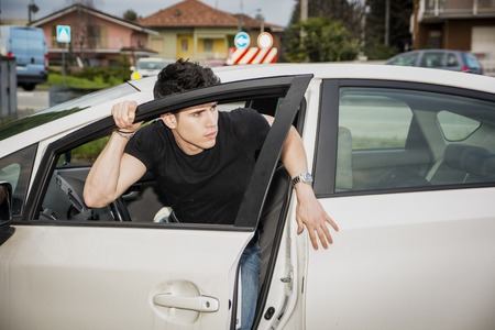 Young attractive man getting out of white car, opening the door Stock Photo