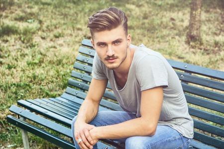 hombre sentado: Joven rubio hermoso que se sienta en verde, banco de parque de madera Foto de archivo