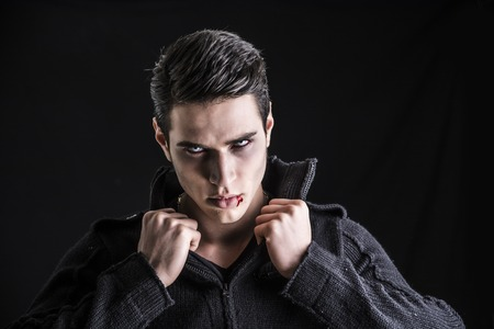 fangs: Portrait of a Young Vampire Man with Black Sweater, Looking at the Camera, on a Dark Smoky Background. Stock Photo
