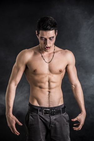 Portrait of a Young Vampire Man Shirtless, Showing his Torso, Chest and Abs, Looking at the Camera, on Dark Background.