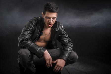 黒い革のジャケットで怒っている負傷した若い男性吸血鬼の肖像