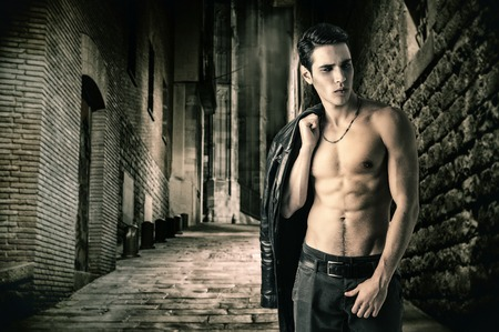 Portrait of a Young Vampire Man in an Open Black Leather Jacket, Showing his Chest and Abs, Looking to Right, on Dark Background. Standard-Bild