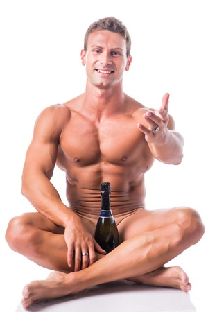 Muscular naked shirtless sexy young man with champagne bottle, sitting on floor, isolated on white background