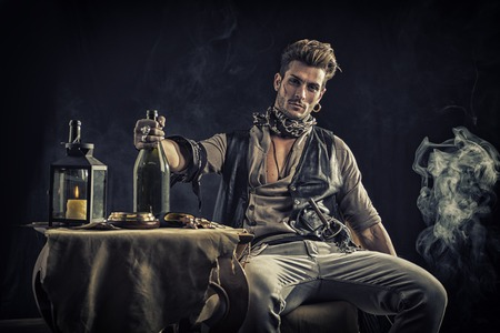rugged: Good Looking Young Man in Pirate Fashion Outfit Sitting next to Table with Candle Lamp, Compass, Gold