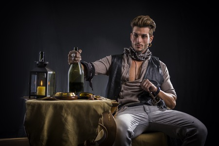 Good Looking Young Man in Pirate Fashion Outfit Sitting next to Table with Candle Lamp, Compass, Gold