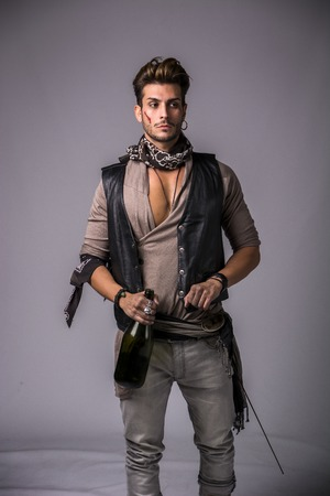 male facial: Good Looking Young Man in Pirate Fashion Outfit on Gray Background. Captured in Studio.