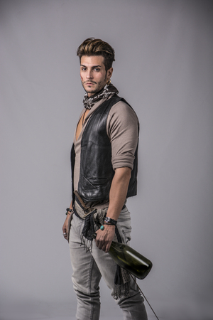men standing: Good Looking Young Man in Pirate Fashion Outfit on Gray Background. Captured in Studio.