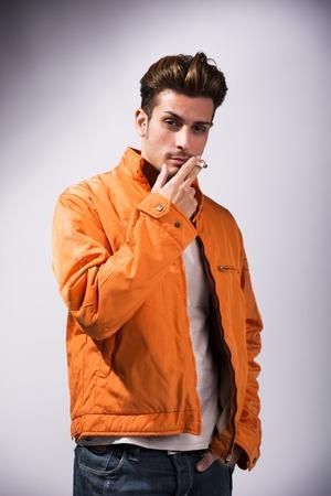 hombre fumando: Joven de cigarrillos que fuma del hombre guapo, vestido como James Dean con la chaqueta roja sobre fondo oscuro Foto de archivo