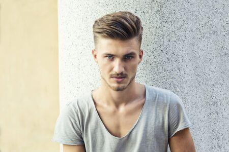 bel homme: Beau jeune homme blond debout en plein air contre le mur de marbre, regardant la caméra Banque d'images