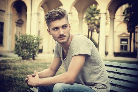 blonde yeux bleus: Beau blond jeune homme assis sur le vert, bois banc de parc Banque d'images