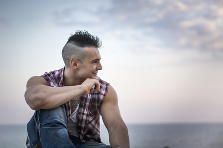 three quarter: Three Quarter Shot of a Handsome Athletic Man in Trendy Attire, Looking Away with Thoughtful Facial Expression Against Sky Background.