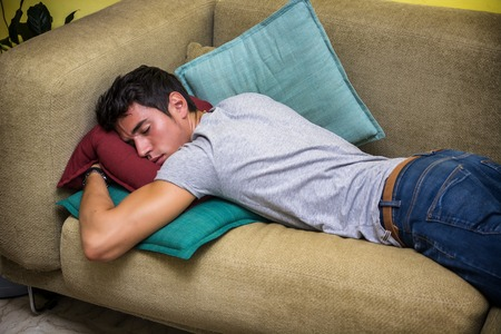 couch: Three Quarter Shot of a Drunk Young Man Sleeping on the Couch in the Home Living Room. Stock Photo