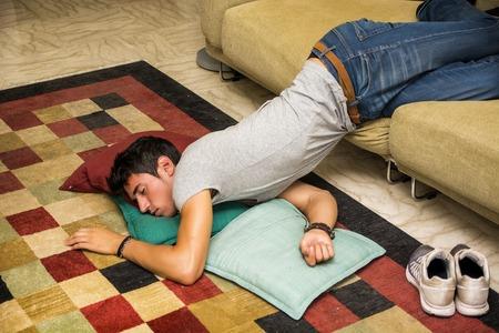 beau jeune homme: Ivre Jeune Handsome Man Reposant sur Couch dans le salon avec tête sur le plancher.
