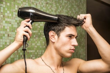 phon: Shirtless young man drying hair with hairdryer, looking at mirror at home Stock Photo
