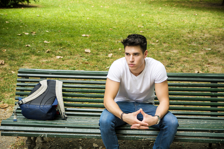 back pack: Young Male Student Sitting on the Bench in a Park, next to his Back Pack, While Thinking and Looking Away Seriously.