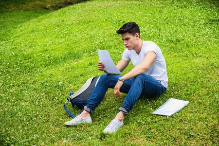 Young Male Student Studying his Lessons while Lying on Grass in City Park, Smiling at Camera Stock Photo