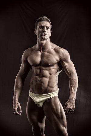 musculoso: Culturista joven muscular en pose relajada, mirando a la cámara. Sobre fondo oscuro, con pantalones cortos