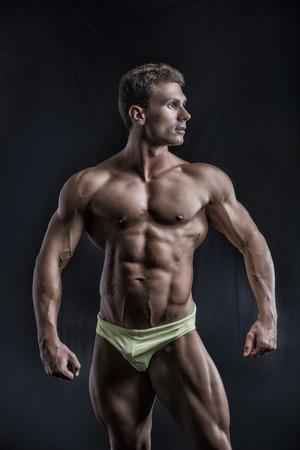 ropa interior: Culturista joven muscular en pose relajada, mirando a un lado. Sobre fondo oscuro, uso de ropa interior