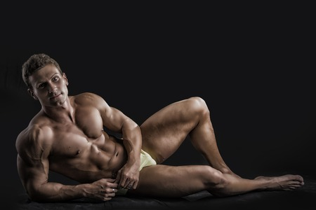Muscular young bodybuilder laying on ground in relaxed pose, smiling and looking at camera. On dark background, wearing shorts