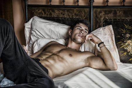 modelos hombres: Sexy modelo masculino descamisado que miente solamente en su cama en su dormitorio, mirando a otro lado con una actitud seductora