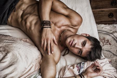 shirtless: Sexy modelo masculino descamisado que miente solamente en su cama en su dormitorio, mirando a la cámara con una actitud seductora