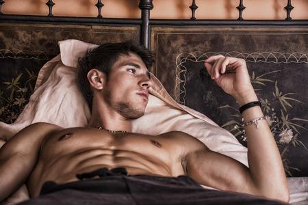 shirtless: Sexy modelo masculino descamisado que miente solamente en su cama en su dormitorio, mirando a otro lado con una actitud seductora