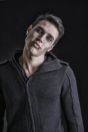 male facial: Portrait of a Young Vampire Man with Black Sweater, Looking at the Camera, on a Dark Smoky Background. Stock Photo