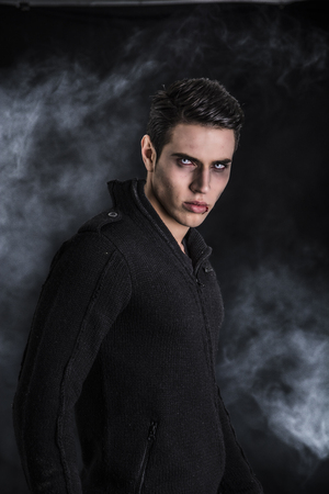 Portrait of a Young Vampire Man with Black Sweater, Looking at the Camera, on a Dark Smoky Background. Zdjęcie Seryjne