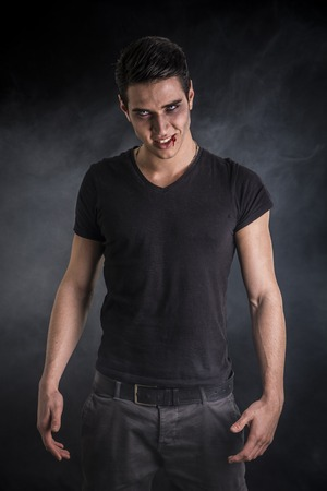 sexy devil: Portrait of a Young Vampire Man with Black T-Shirt, Looking at the Camera, on a Dark Smoky Background.