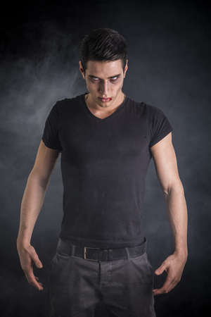 vampire teeth: Portrait of a Young Vampire Man with Black T-Shirt, Looking at the Camera, on a Dark Smoky Background.