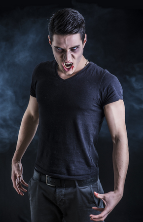 Portrait of a Young Vampire Man with Black T-Shirt, Looking at the Camera, on a Dark Smoky Background.