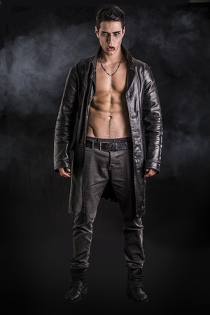 male model torso: Portrait of a Young Vampire Man in an Open Black Leather Jacket, Showing his Chest and Abs, Looking at the Camera, on Black Background.
