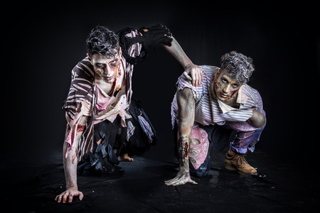 Two male zombies crawling on their knees, on black smoky background, looking at camera. Halloween theme Standard-Bild