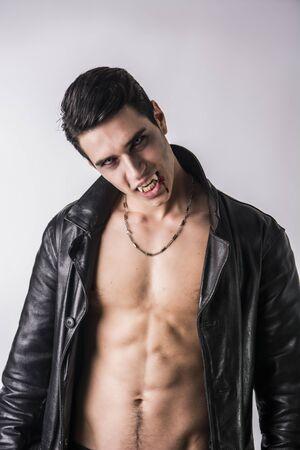 fiend: Portrait of a Young Vampire Man in an Open Black Leather Jacket, Showing his Chest and Abs, Looking at the Camera, on a White Background.