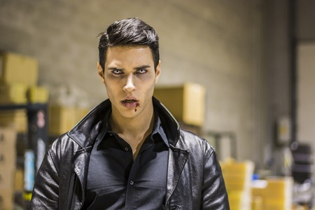 Close up Face of a Handsome Vampire Man in Leather Clothing, with Blood on his Mouth, Looking at the Camera.