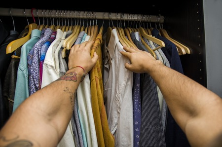 the first: Man searching for a shirt hanging on the rail in his wardrobe, first person point of view looking down his arms. Self POV