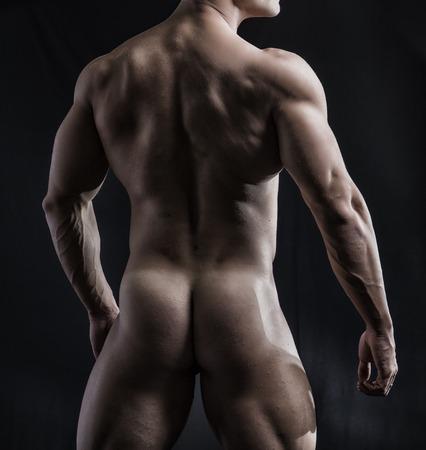 nudo maschile: Corpo di Fit uomo completamente nudo di fronte retro, esposizione Glutei e posteriore, su sfondo scuro.