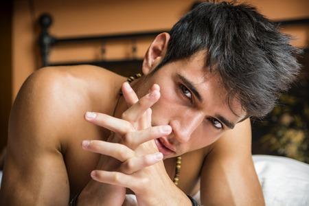 sin camisa: Sexy modelo masculino descamisado que miente solamente en su cama en su dormitorio, mirando a la cámara con una actitud seductora
