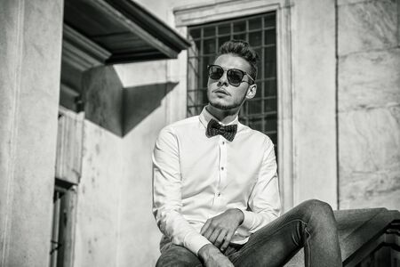 half body: Attractive young man sitting next to walls in city, looking away, wearing sunglasses. Half body shot