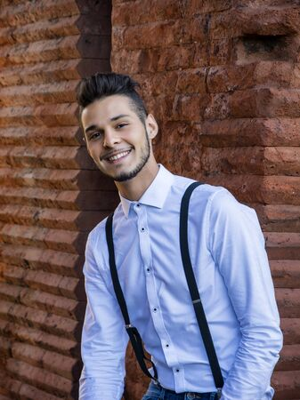 quarters: Attractive young man sitting against brick wall, looking at camera smiling. Three quarters shot Stock Photo