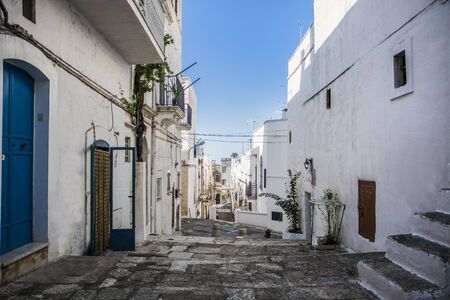white washed: Narrow Cobblestone Alley Between White Washed Mediterranean Houses on Hill Side in Ibiza, Spain on Sunny Day with Blue Sky