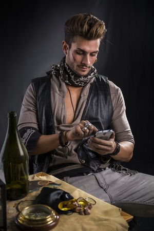 beside table: Fashionable Man Dressed as Pirate, with Cell Phone Wearing Leather Vest and Scarf Sitting in Chair Beside Table, with Empty Bottle and Various Items Stock Photo