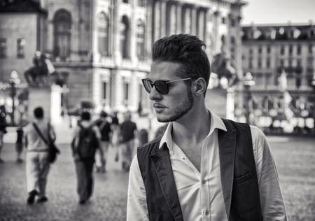 modelos posando: Encuadre cintura para arriba Retrato de moda de hombre joven con gafas de sol y de pie al aire libre en la histórica Plaza de la ciudad y mirando con expresión seria al Lado