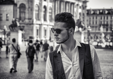 urban style: Waist Up Portrait of Fashionable Young Man Wearing Sunglasses and Standing Outdoors in Historical City Square and Gazing with Serious Expression to the Side
