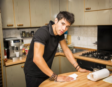 doing chores: Attractive Young Man with Dark Hair, Looking at Camera While Cleaning Off Surface of Kitchen Table with Paper Towel - Responsible Young Man Doing Chores, in First Home Stock Photo