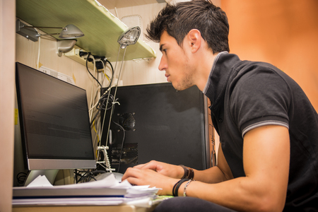Waist Up Profile of Young Attractive Man with Dark Hair, Sitting at Computer Desk Working on Paper Homework or on His Start-up Business, in Dorm Room Foto de archivo
